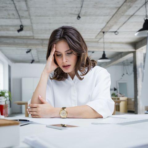 Female entrepreneur with headache sitting at desk