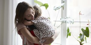 Female fashion designer embracing daughter while standing by window at home