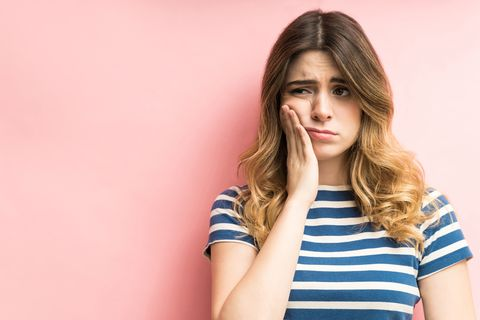 female feeling painful toothache against plain background