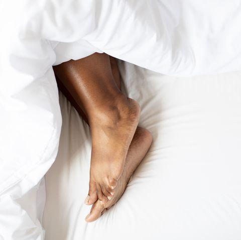 female feet under blanket