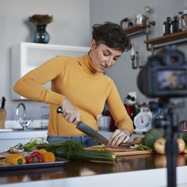 Female food vlogger making video while prepping vegetables in kitchen