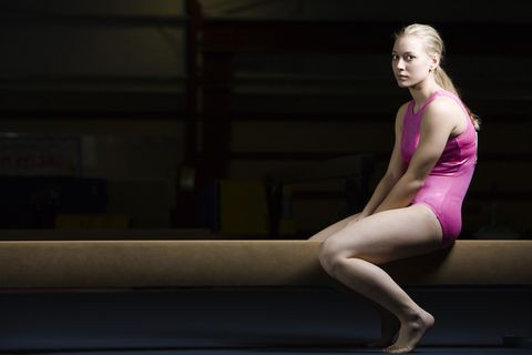 Female gymnast sitting on balance beam, disappointed look on face