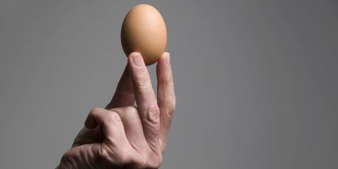 female hand holding an egg