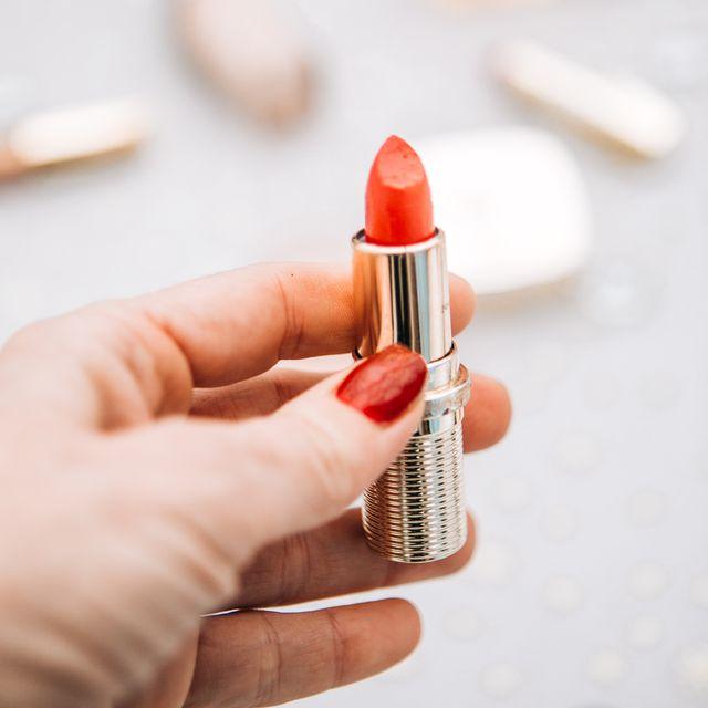 mujer sosteniendo un labial rojo