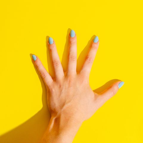 Female Hand on Yellow Background