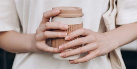 female hands hold reusable coffee mug