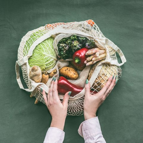female hands holding eco friendly mesh shopping bag with vegetables