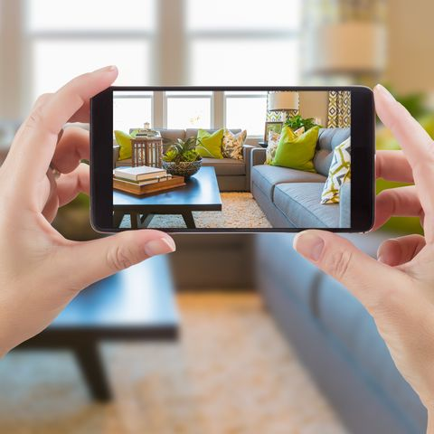 female hands holding smart phone displaying photo of house interior living room behind