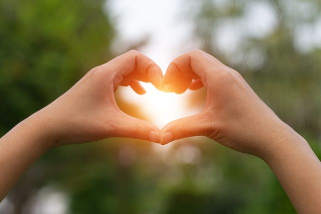 female hands in the form of heart against the sky pass sun beams hands in shape of love heart