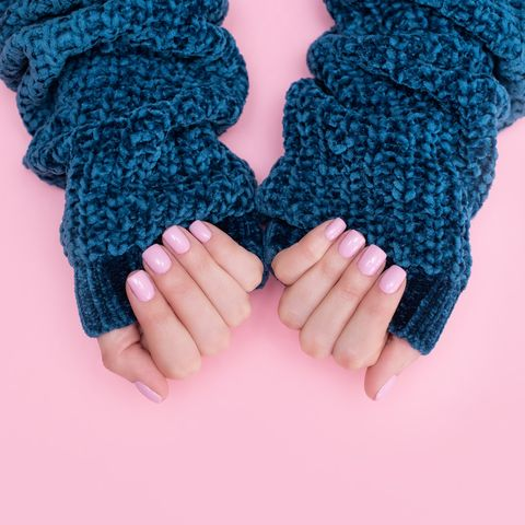 female hands manicure close up view on pink knitted sweater background nail painting effects manicure salon banner concept