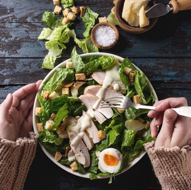 female hands take by fork classic caesar salad with chicken breast in white ceramic plate served with ingredients above over old dark blue wooden background flat lay rustic style