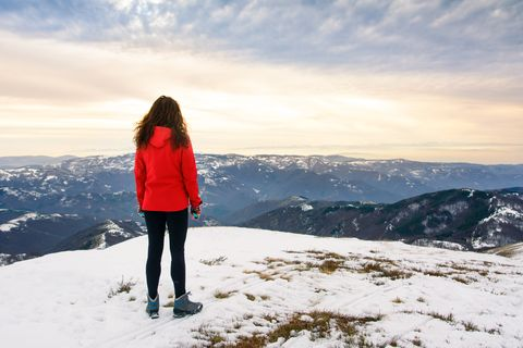 female hiker on snow covered mountain top