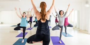 Female instructor with yoga class in the gym