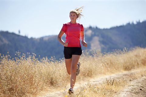 A female jogging down a dirt road.