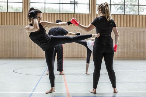 female kickboxers practising in sports hall