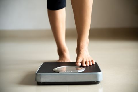 female leg stepping on weigh scales healthy lifestyle, food and sport concept