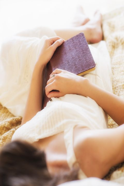 Woman in white chemise laying in bed and holding book