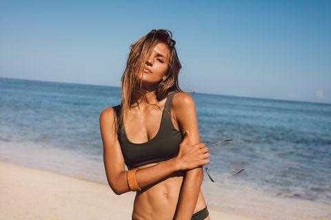 female model posing in swimsuit on the sea shore