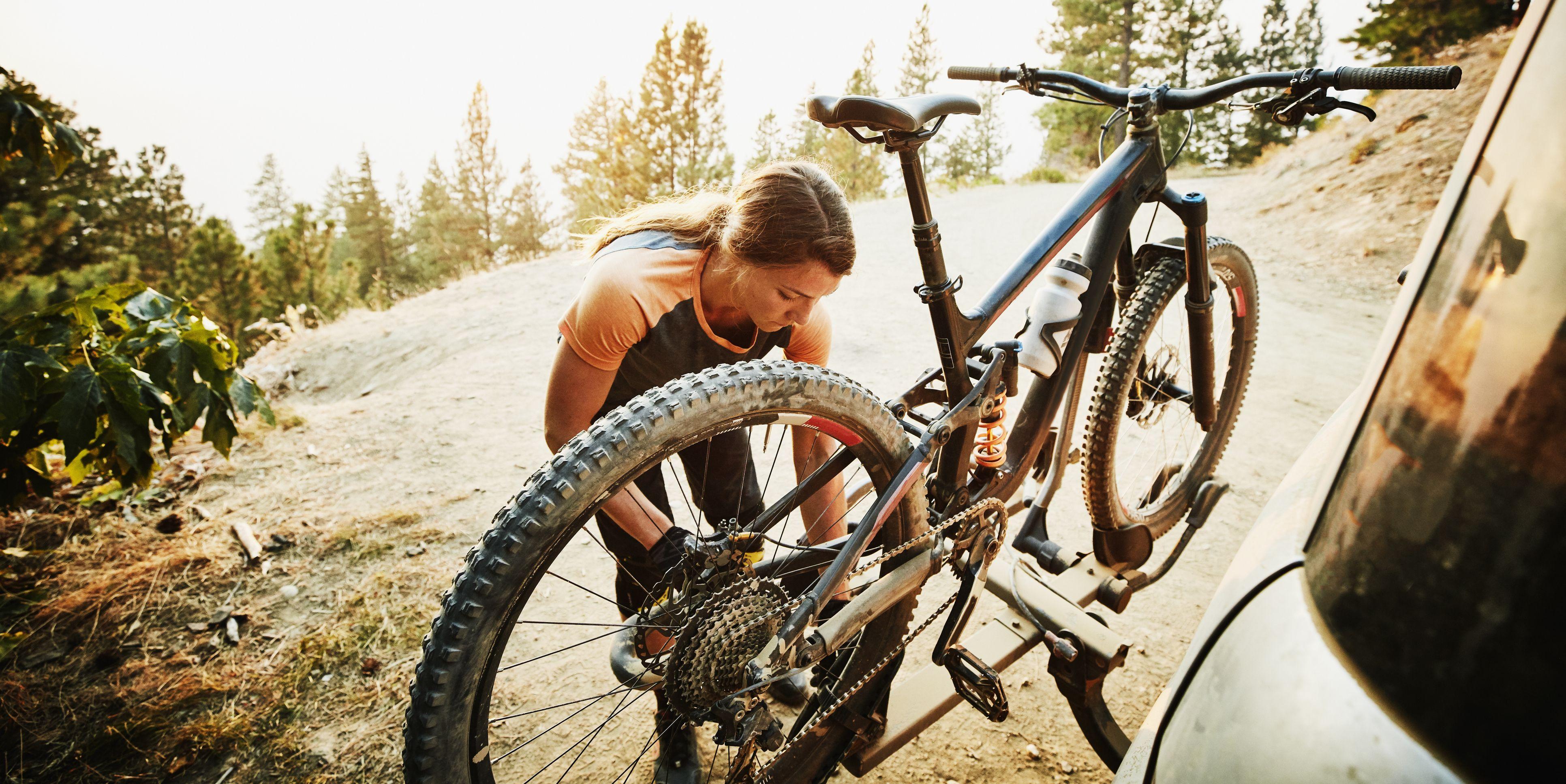 Female mountain biker putting bike on car after ride on summer evening