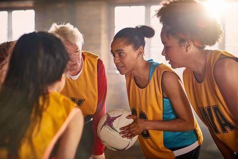 Female netball team talking in gym.