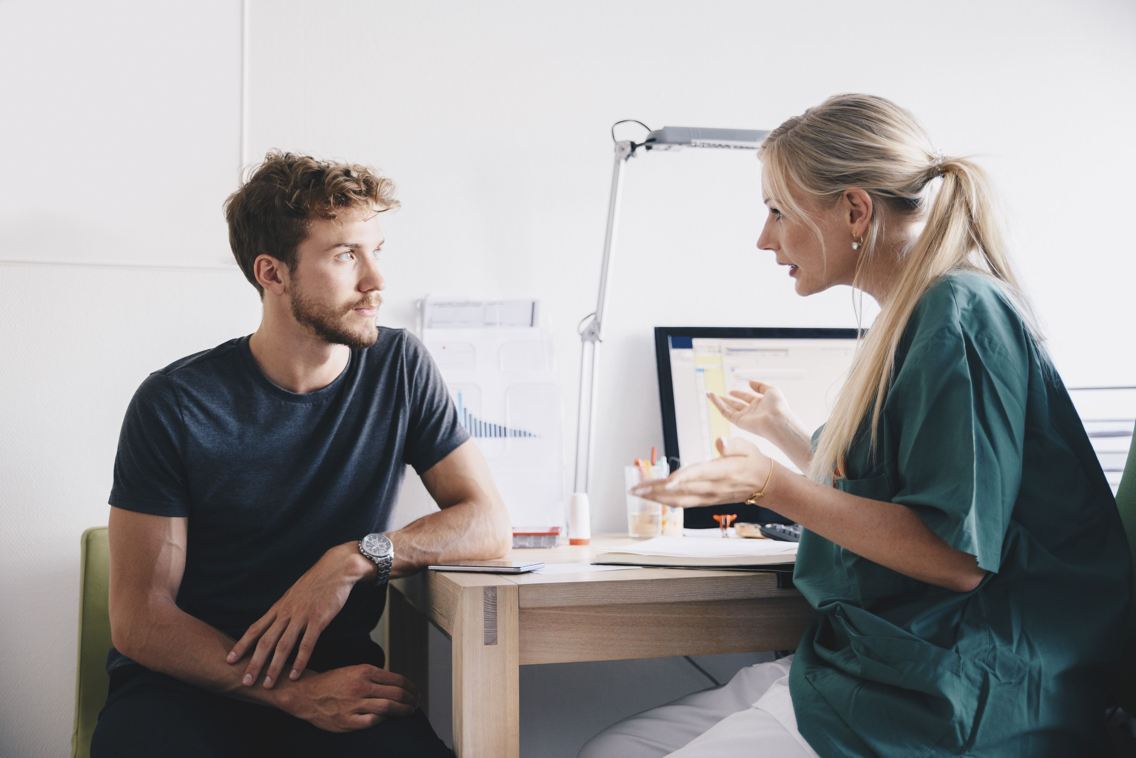 Female nurse explaining to young male patient at office in hospital