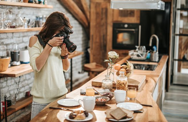 female photographer taking photos of food at dining table