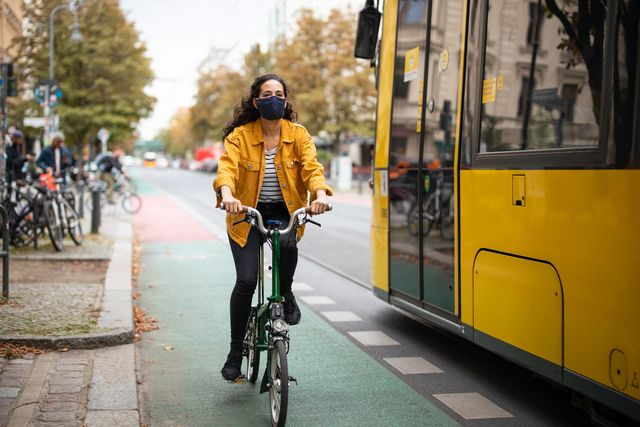 female riding a cycle wearing face mask in the city