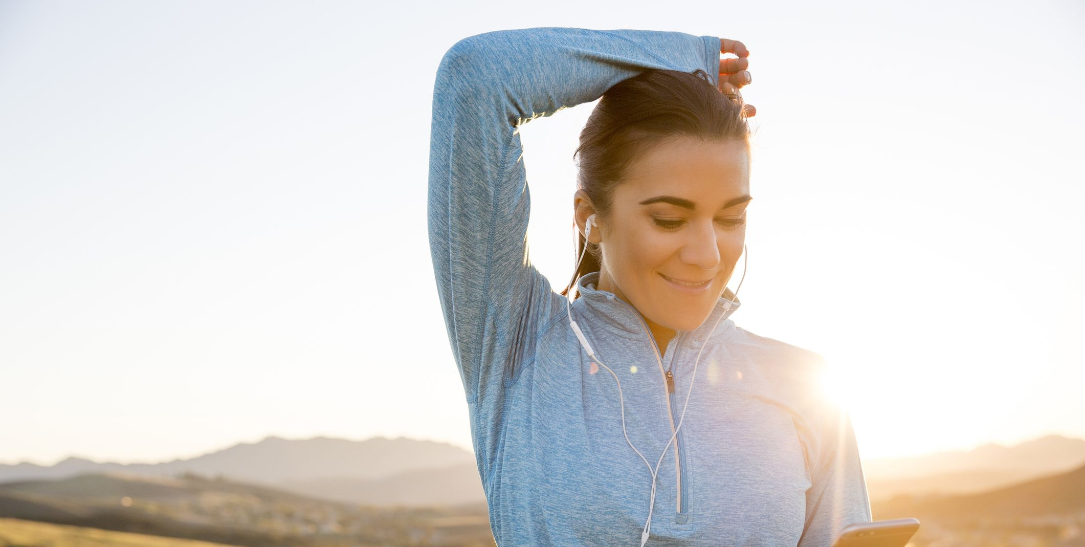 Female runner choosing smartphone music on mountain trail at sunset