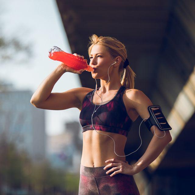 female runner having break and drinking refreshment drink