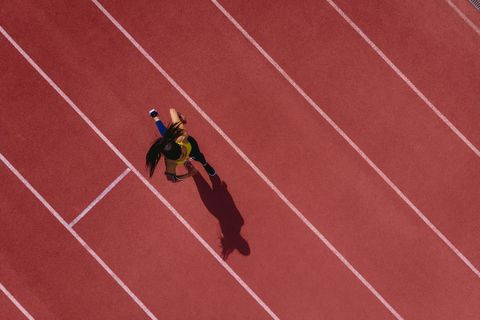 Female runner listening to music and running on sports track