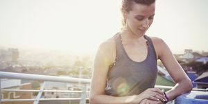 Female runner resting checking smart watch fitness tracker on sunny urban footbridge