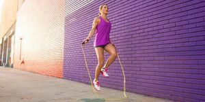 Female runner skipping on sidewalk