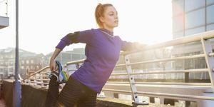female runner stretching leg in urban space.
