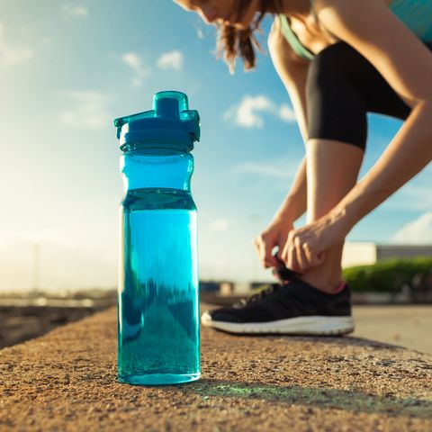 Female runner tying her shoes next to bottle of water