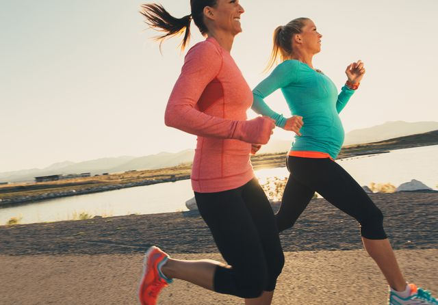 female runners on a trail at sunset