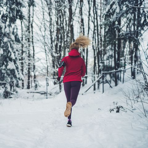 female running in forest at winter day