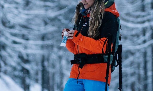 female snowshoer enjoys snack in snowy forest