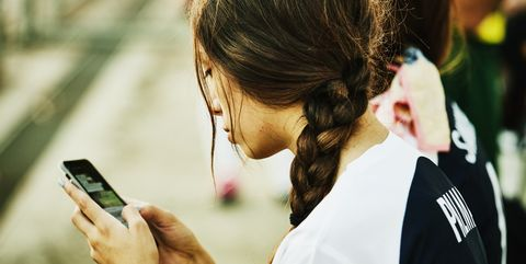 Female soccer player checking smart phone after soccer match