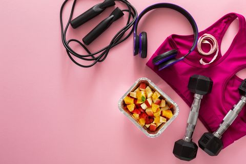 Female sport clothing and fruit salad top view