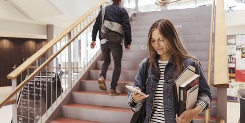 Female student using mobile phone while man walking up on steps in university