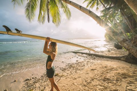 Female surfer carrying surfboard on head, tropical beach at sunset