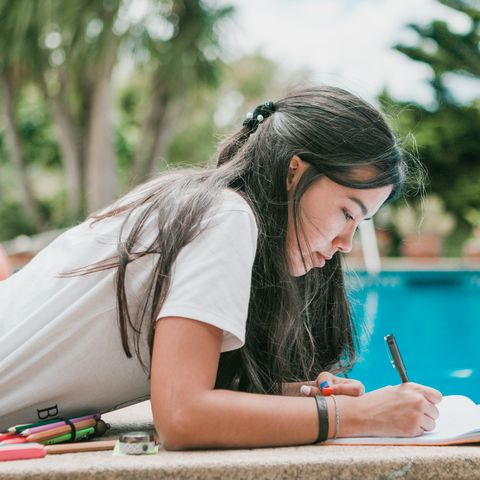 female teenager doing homeworks in back yard in a sunny day