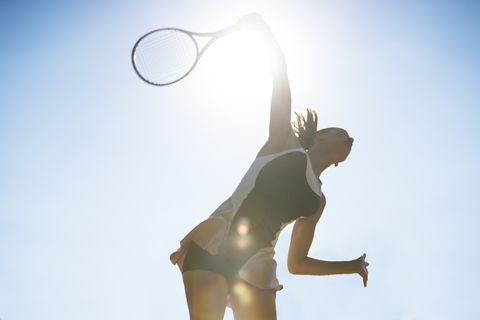 female tennis player about to hit a serve