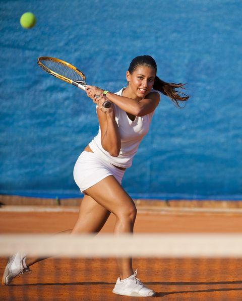 female tennis player hitting the ball