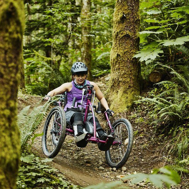 female wheelchair athlete descending trail on adaptive mountain bike