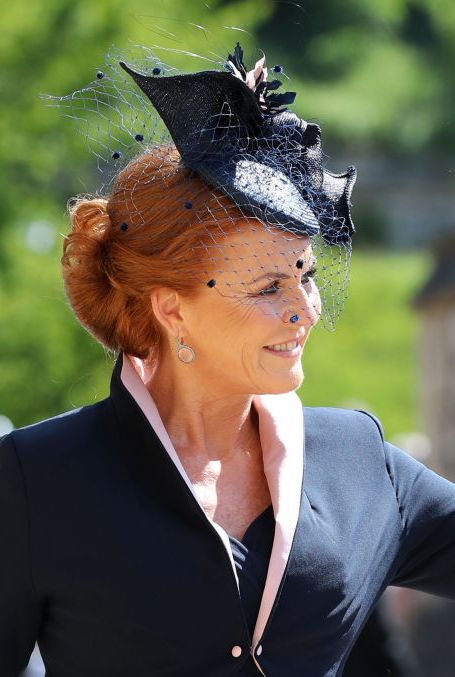 The Duchess of York is wearing a navy dress and matching jacket with white piping by Emma Louise Design. Her hat and veil were designed by milliner Jess Collett.