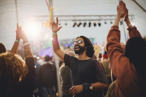 people are dancing in a performance tent at a music festival the main focus is on a man who is wearing sunglasses and is dancing with a hand in the air