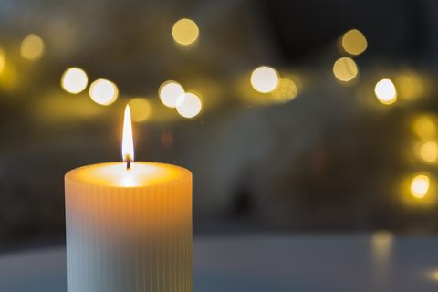 festive background with burning candle and bokeh