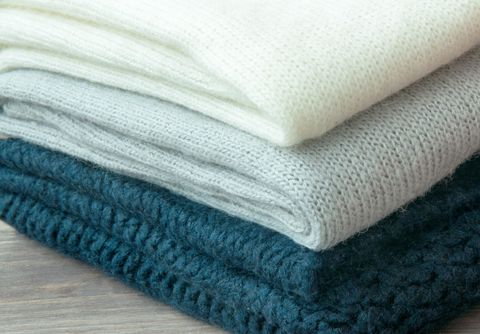 A few stacked warm knitted sweaters, lying on a wooden background. The concept of  warm.