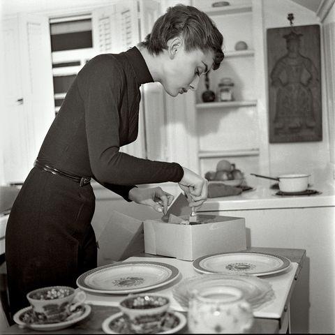 ヒット作となった『麗しのサブリナ』の撮影中に借りていたウィルシャー通りのアパートにて。ケーキを切り分けるオードリー。1953年。